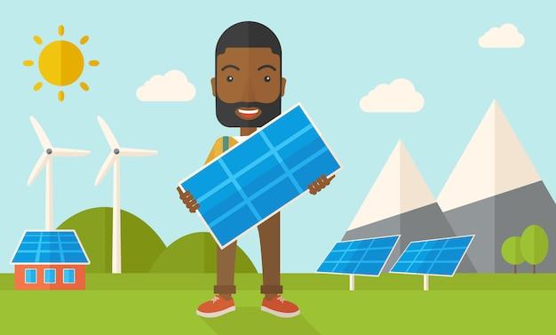 Uomo africano che tiene un pannello solare.