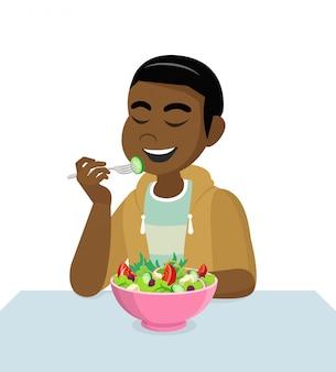 L'uomo africano sta mangiando un'insalata.