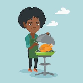 Donna africana che cucina pollo sul barbecue.