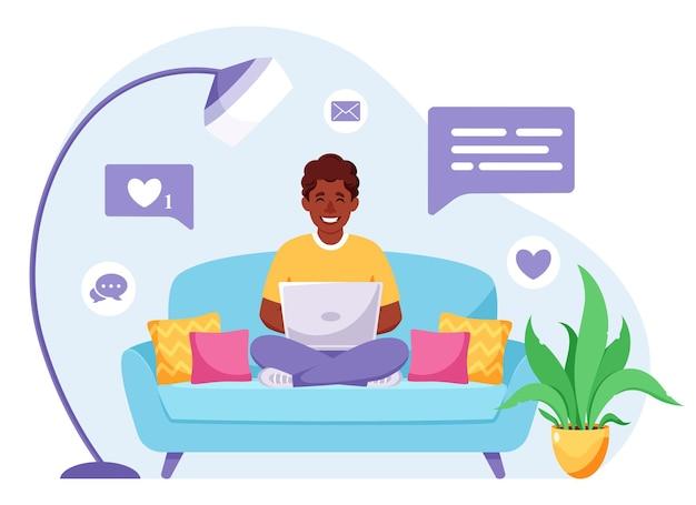 Uomo afroamericano che si siede su un divano e lavora al computer portatile