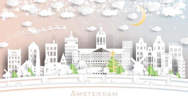 Orizzonte della città di amsterdam olanda in stile taglio carta con fiocchi di neve, luna e ghirlanda al neon.
