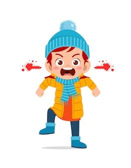 Il ragazzino sveglio arrabbiato urla e indossa una giacca nella stagione invernale