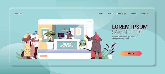 Uomini d'affari arabi clienti o viaggiatori in piedi alla reception online e parlando con l'addetto alla reception in orizzontale