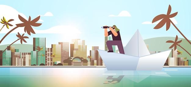 Uomo d'affari arabo con un binocolo che galleggia su una barca di carta in cerca di una pianificazione strategica di avvio della leadership futura di successo