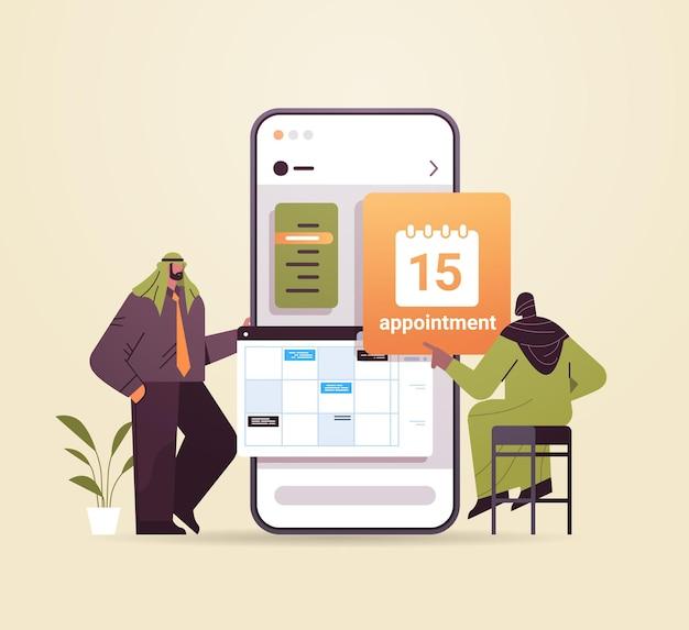 Imprenditori arabi che pianificano l'appuntamento per la pianificazione del giorno nel calendario sulla gestione del tempo dello schermo dello smartphone