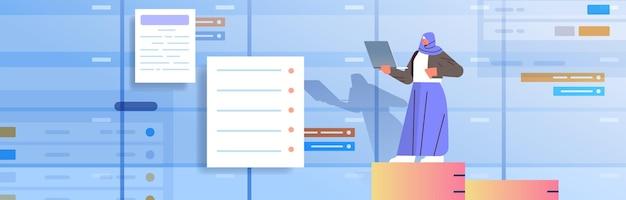 Imprenditrice araba che lavora al concetto di gestione del tempo multitasking di pianificazione aziendale del computer portatile