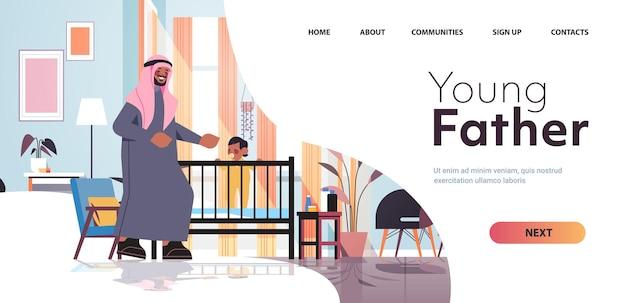 Padre arabo che gioca con il piccolo figlio nella culla paternità genitorialità concetto papà trascorrere del tempo con il suo bambino a casa camera da letto interno a figura intera orizzontale copia spazio illustrazione vettoriale