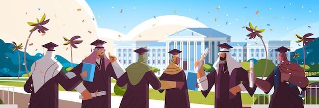 Studenti laureati arabi in piedi insieme vicino all'università che costruiscono laureati arabi che celebrano il diploma accademico laurea concetto di educazione ritratto orizzontale illustrazione vettoriale