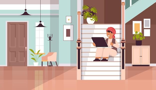 Scolaro arabo che utilizza laptop arabo ragazzo seduto sulla scala e facendo i compiti concetto di educazione