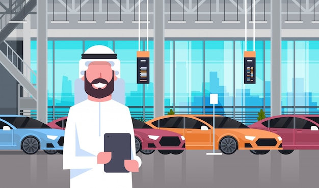 Uomo arabo del venditore nell'automobile showroom del centro di concessionaria interno sopra l'insieme di nuovi veicoli moderni