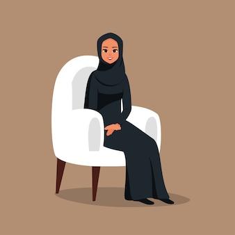 La donna araba in hijab è seduta su una comoda poltrona