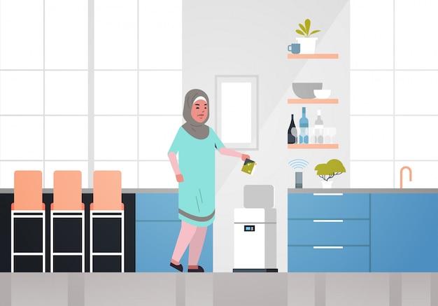 Donna araba che mette i rifiuti nel cestino elettronico controllato