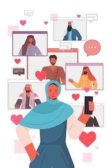 Donna araba che utilizza smartphone che chiacchiera nell'app di datazione online con gli uomini arabi nell'illustrazione di verticale di concetto di comunicazione di relazione sociale delle finestre del browser web