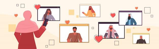 Donna araba che utilizza smartphone che chiacchiera con gli uomini della corsa della miscela nell'illustrazione orizzontale del ritratto di concetto di relazione sociale delle finestre del browser web online di app