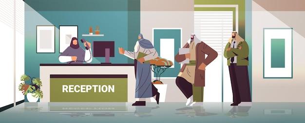 Uomini d'affari arabi clienti o viaggiatori in piedi alla reception e parlando con l'addetto alla reception illustrazione vettoriale a figura intera orizzontale