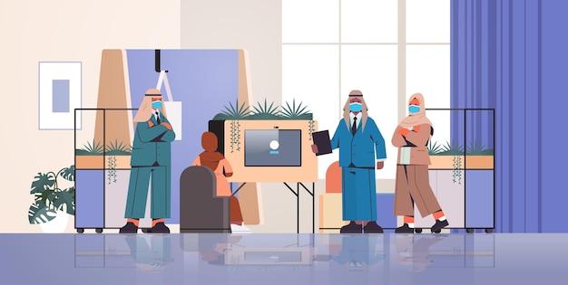 Uomini d'affari arabi in maschere che fanno presentazione nel concetto di lavoro di squadra pandemico del coronavirus centro di coworking creativo