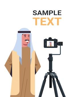 Blog arabo dell'uomo che registra video blog con la macchina fotografica digitale sul treppiede lo streaming verticale della copia del ritratto di concetto di blogging di media sociali in streaming in diretta