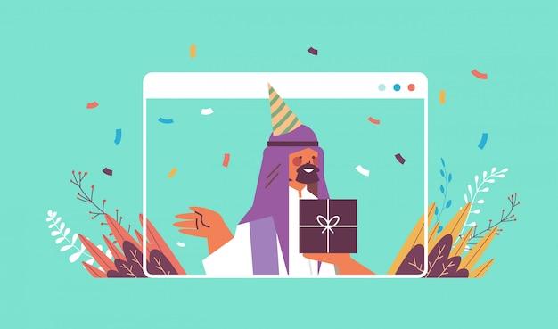 Uomo arabo in cappello festivo che celebra il concetto di quarantena di isolamento di auto celebrazione della festa di compleanno online