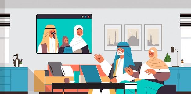 Genitori arabi e figlia che hanno riunione virtuale con i nonni durante l'illustrazione orizzontale di orizzontale del ritratto interno del salone di concetto di comunicazione di chiacchierata della famiglia di video chiamata