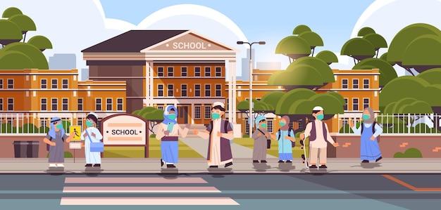 Scolari arabi che indossano maschere per evitare che gli alunni della pandemia di coronavirus stiano insieme vicino all'edificio scolastico