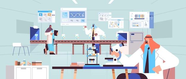 Scienziati arabi che cercano di microscopio team di ricercatori arabi che effettuano ricerche microbiologiche in laboratorio test del dna diagnosi di ingegneria genetica