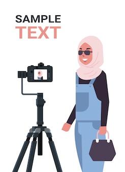 Blog arabo della donna che registra video blog con la macchina fotografica digitale sul treppiede lo streaming verticale della copia del ritratto di concetto di blogging di media sociali in streaming in diretta