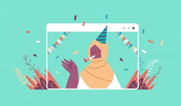 Donna araba in cappello festivo che celebra il concetto di quarantena di isolamento di auto celebrazione della festa di compleanno online