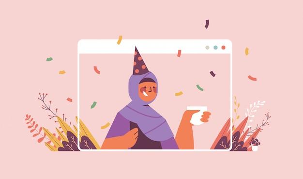 Donna araba in cappello festivo che celebra in linea la celebrazione della festa di compleanno auto isolamento quarantena