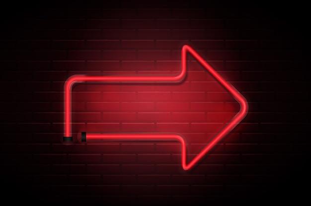 Freccia incandescente tubi rossi al neon sul muro di mattoni scuri.