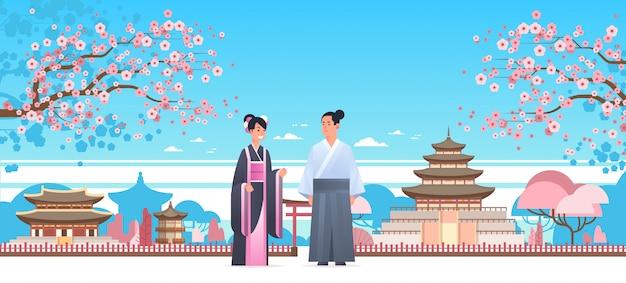 Coppia asiatica che indossa abiti tradizionali uomo donna in costume antico in piedi insieme caratteri cinesi o giapponesi su edifici pagoda paesaggio
