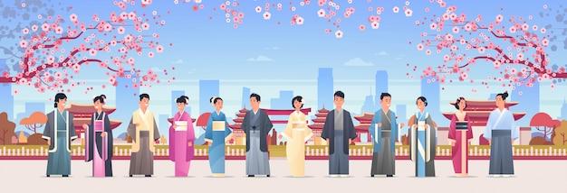 Gruppo di persone asiatiche in abiti tradizionali uomini donne che indossano costumi antichi in piedi insieme caratteri cinesi o giapponesi su edifici pagoda paesaggio