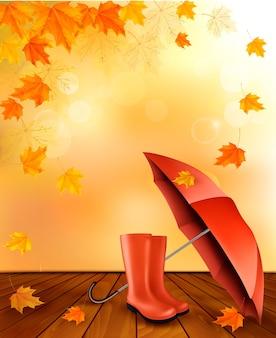 Sfondo autunnale con ombrello e stivali da pioggia.