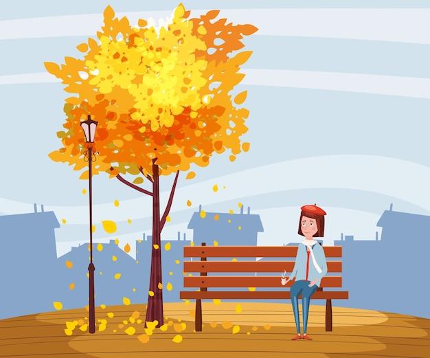 Autunno, ragazza felice che si siede su una panchina con una tazza di caffè, sotto un albero con foglie che cadono in un parco, città, urbano