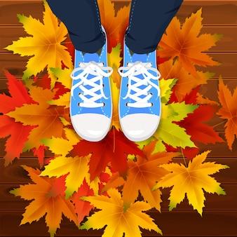 Modello di sfondo di foglie di autunno con vista dall'alto di gambe di foglie di acero in scarpe da ginnastica su foglie che cadono colorate.