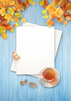 Sfondo autunno vista dall'alto con fogli bianchi di carta e tazza da tè di vetro