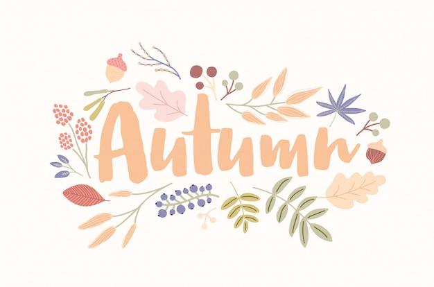 Parola autunnale scritta a mano con elegante carattere corsivo decorato con foglie di alberi caduti, fiori secchi, ghiande, bacche.