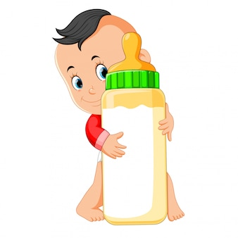 Il bambino felice giocando e abbraccia la bottiglia di latte