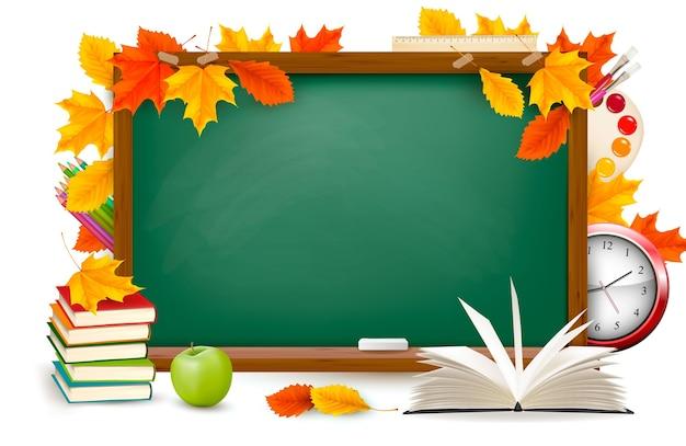 Di nuovo a scuola. scrivania verde con materiale scolastico e foglie d'autunno. .