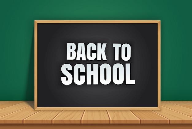 Ritorno a scuola con lavagna nera sul tavolo di legno.