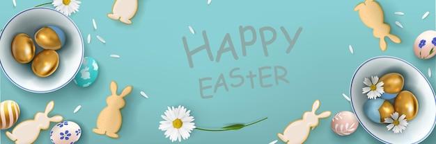 Banner con uova di pasqua in una ciotola di ceramica con fiori e biscotti a forma di lepri sullo sfondo.