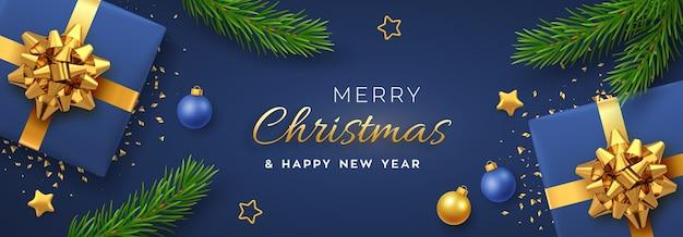 Banner con scatole regalo blu realistiche con fiocco dorato, stelle dorate, palline e rami di pino