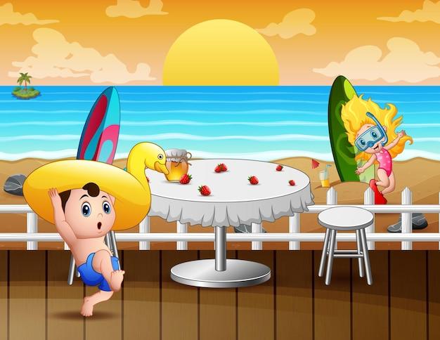 Paesaggio del ristorante o del caffè sulla spiaggia con bambini felici che giocano