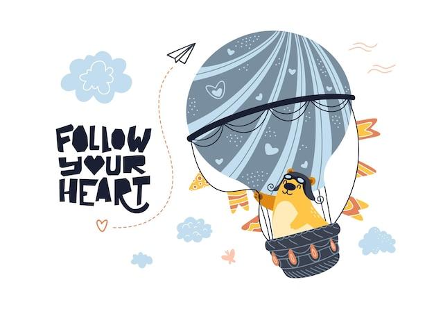 Orso che vola in mongolfiera. lettering segui il tuo cuore.