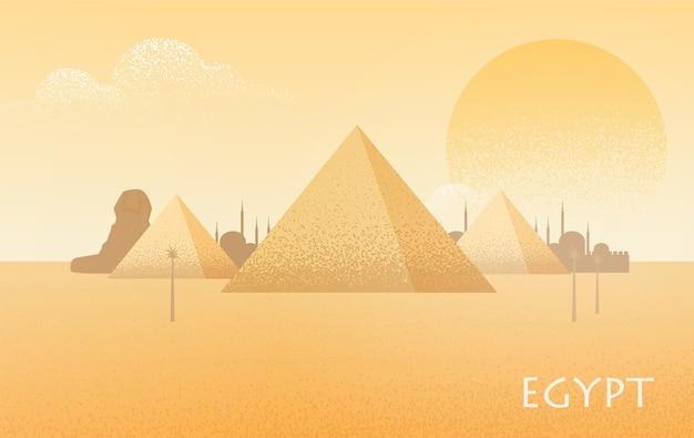 Bellissimo paesaggio desertico dell'egitto con sagome del complesso della piramide di giza, statua della grande sfinge, edifici tradizionali e grande sole cocente sullo sfondo