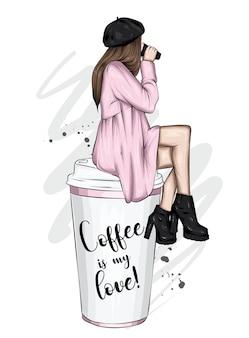 Una bella ragazza con un cappotto si siede su un bicchiere di caffè.