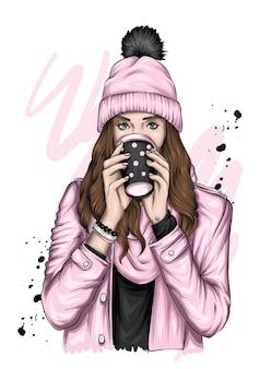 Una bella ragazza con un piumino e un cappello con un bicchiere di caffè. natale.