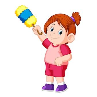 Bella ragazza che tiene lo spolverino per pulire la polvere