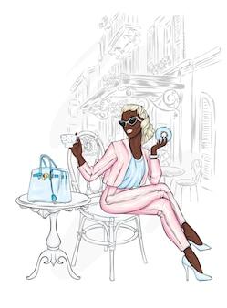 Bella ragazza in abiti eleganti e caffè di strada