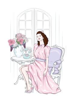 Bella ragazza con un vestito elegante e una poltrona vintage