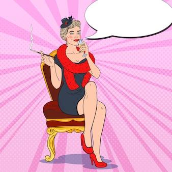 Bella donna che fuma con un bicchiere di champagne